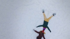Young girls do a snow angel on a sunny winter day. Slow motion. 4K. Stock Footage