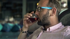 Happy, young man relaxing and drinking Sangria wine in cafe Stock Footage