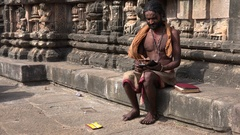 India technology and tradition, holy man uses smartphone in temple Stock Footage