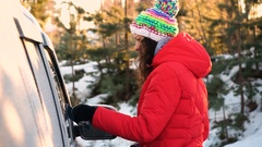 Woman remove snow and ice from car Stock Footage