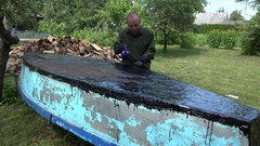 Craftsman man with gas burner and tar repair his boat. 4K Stock Footage