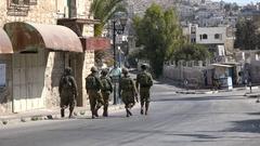 Israeli army unit patrols empty streets of Hebron settlement West Bank Stock Footage