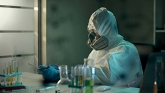 Elderly skilled scientist in protective uniform and mask transfers or copies the Stock Footage