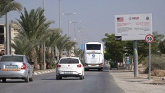 Traffic drives into Jericho past a USAID sign, in the West Bank Stock Footage