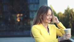 Young beautiful girl in a yellow jacket near office staying and smiling at the Stock Footage