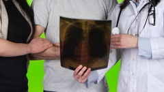 Woman doctor shows radiograph married couple. Closeup. Green screen Stock Footage