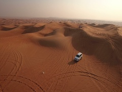 Aerial view of 4x4 off vehicle taking tourists on desert dune bashing safari Stock Footage