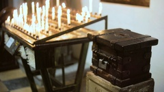 Donation box near burning candles in a church Stock Footage