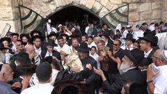 Orthodox Jews dance around a Torah scroll, Western Wall in Jerusalem, Israel Stock Footage