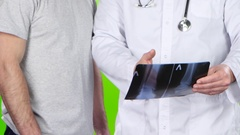 Male doctor and a man patient discussing roentgenogram. Green screen Stock Footage