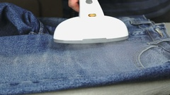 Process of steaming of jeans using steam cleaner Stock Footage