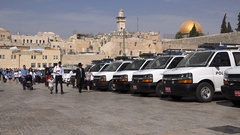 Jewish families walk past police vehicles at Western Wall in central Jerusalem Stock Footage