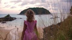 Happy 5 year old girl raises up hands like wings on a hill above the ocean at Stock Footage