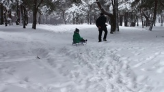 Grandpa rolls his little grandson of the snowy winter forest on a sledge Stock Footage