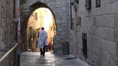 Religious Jewish man leaves synagogue, walks through old city Jerusalem Stock Footage