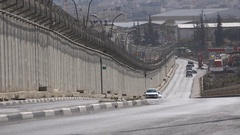 Traffic drives past the separation wall between Israel and the West Bank Stock Footage