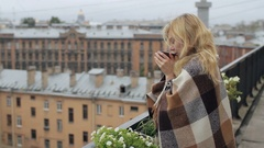 Girl Sheltered Blanket With Tea on the Balcony Overlooking the City Stock Footage