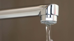 Water under weak pressure flows from a water tap Stock Footage