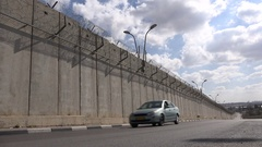 Heavy truck drives past Israel West Bank security barrier Stock Footage
