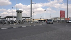 Traffic drives through Qalandia checkpoint between Jerusalem and Ramallah Stock Footage