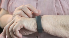 Elderly woman touches wristband of pulse monitor Stock Footage
