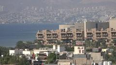 The skyline of Eilat (Israel) visible behind buildings in Aqaba (Jordan) Stock Footage