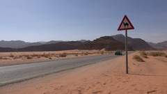 Taxii drives past a hazard sign against camels in Jordan Stock Footage