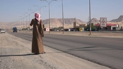 Traditionally dressed Arab man waits for bus on Desert Highway Jordan Stock Footage