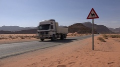 Traffic drives through the Jordanian desert, past a sign warning for camels Stock Footage