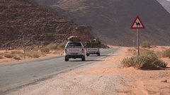 Jeeps drive through Wadi Rum desert, past warning sign for camels Stock Footage