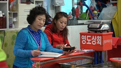 Two South Korean women do accounting in fish market in Busan Stock Footage