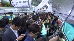 Railway passengers ride a busy commuter train in Seoul, South Korea Stock Footage