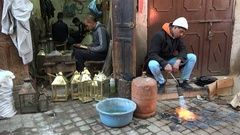 Blacksmiths use fire and other tools in workshop Marrakech bazaar, Morocco Stock Footage