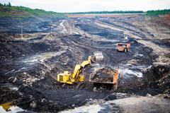 Mining dump trucks working in Lignite coalmine Stock Photos