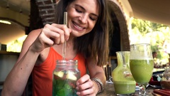Happy woman mixing fruity juice in cafe, super slow motion 240fps Stock Footage