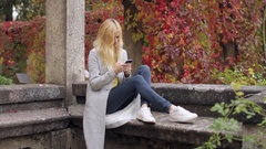 Woman Writes a Message on a Smartphone While Sitting on a Stone Bench in the Stock Footage