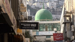 Contrast Western financial institution and mosque Nablus, West Bank Stock Footage