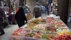 People walk past a candy shop in the Nablus bazaar in the West Bank Stock Footage