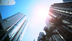 Smooth low angle tracking shot of office buildings with sun flare reflection. Stock Footage
