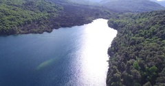Aerial drone scene of lake at sunset, volcanic lava river from volcano Stock Footage