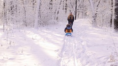 A young mother takes her child on a sled on a snowy alley. Stock Footage