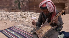 Bedouin man plays traditional music for tourists in Petra Stock Footage