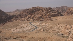 Cars drive through stunning mountain ranges in deserts of Jordan (Middle East) Stock Footage