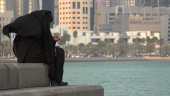 Conservative Muslim woman uses a smartphone in central Doha, Qatar Stock Footage