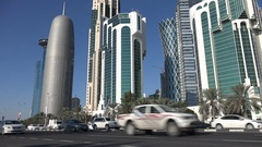 Traffic drives past the modern skyline of central Doha, Qatar Stock Footage