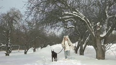 Slowmotion Happy girl playing with her dog on snow and having fun outside winter Stock Footage
