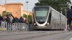 Modern tram rides past walls of medina central Rabat Stock Footage