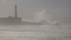 Waves crash on the shore in front of lighthouse Rabat in Morocco Stock Footage