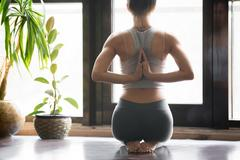 Young woman in vajrasana pose, home interior background, namaste Stock Photos