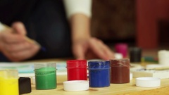 Jars of gouache are on the table against depicting girls dressed in white. Stock Footage